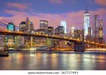 Manhattan skyscrapers and Brooklyn Bridge - beautiful gentle colors of sky and city illuminations, New York, USA  - stock photo