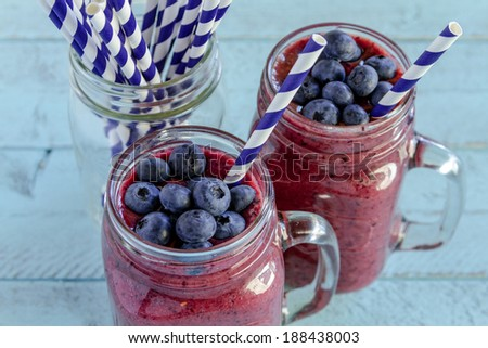 2 Mason jars filled with blueberry and blackberry fresh fruit smoothie sitting on blue wood background with straws - stock photo