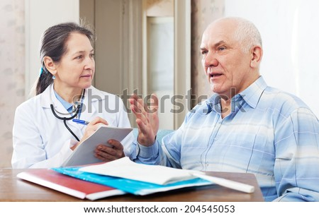 mature doctor talks with sick senior man at near table with documents - stock photo