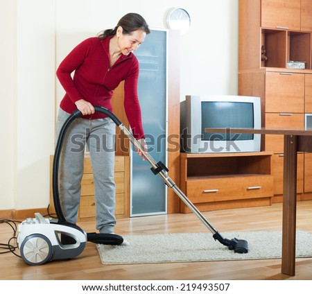 mature woman cleaning with vacuum cleaner on parquet floor - stock photo