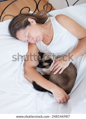 Mature woman sleeping in   embrace with   cat in   bedroom. - stock photo