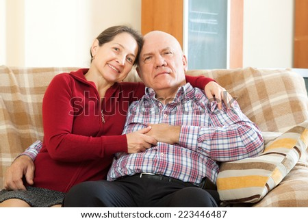 mature woman with smiling husband in home interior - stock photo