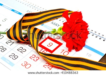 9 May concept. Postcard for Victory Day celebration - red carnation wrapped with George ribbon lying on the calendar with framed 9 May date  - stock photo