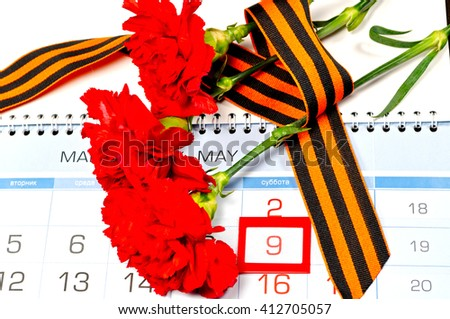 9 May concept. Victory Day still life - red carnations wrapped with George ribbon on the calendar with 9th May date- holiday commemorating the victory of Soviet Union in the Great Patriotic War.  - stock photo
