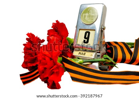 9 May concept. Vintage metal desk calendar with 9th May date and George ribbon with red carnations bouquet  isolated on white background. Selective focus at the calendar. 9 May still life.  - stock photo