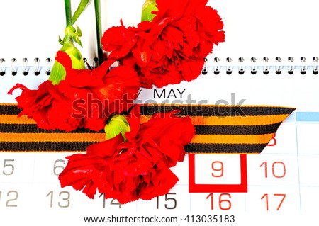 9 May festive still life. St George ribbon and red carnations above the calendar with 9 May date - the day of victory in Great Patriotic War in Russia - stock photo