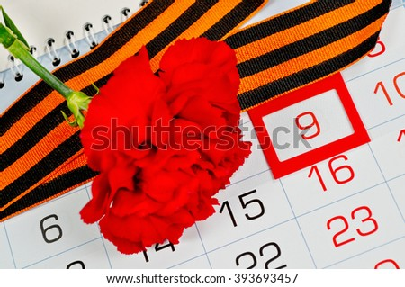 9 May greeting card - bright red carnation with George ribbon lying on the calendar with 9th May date. 9 May concept.  - stock photo