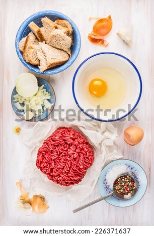 meat patties Ingredients: raw  minced meat , raw egg,chopped onion,garlic,bread,salt and pepper on white wooden background - stock photo