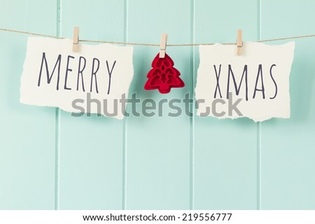 """Merry xmas"" and a felt tree hanging on a rope with clothespins. A robin egg blue wainscot as background. Vintage Style. - stock photo"