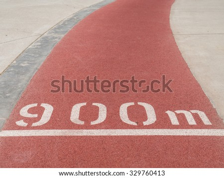 900 metre mark on a rubberised red running track. - stock photo