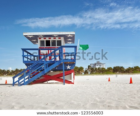 Miami Beach Florida, lifeguard house in a typical colorful Art Deco style,painted in the American flag colors on a summer day, with blue sky and Ocean in the background. Famous travel location. - stock photo