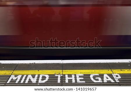 """Mind the gap"", London tube platform edge (Painted warning on the floor). - stock photo"