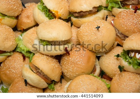 Mini hamburgers with cheese and sesame seeds in buffet corner  - stock photo