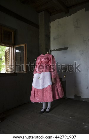 Mixed media artwork. Headless woman in the folk costume standing in the gloomy room, surrounded by butterflies. - stock photo