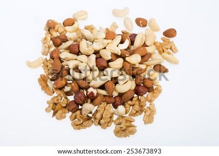 mixed nuts  -  hazelnuts, walnuts, cashews,  pine nuts isolated on white background - stock photo