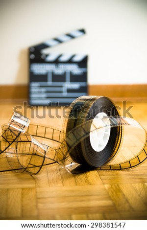 35 mm cinema film reel and out of focus movie clapper board in background on wooden floor vertical frame - stock photo