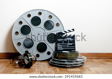35 mm cinema movie roll and reels with clapper and filmstrip on wooden floor and white wall background - stock photo