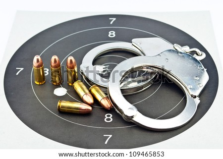 9mm Luger Ammunition and Handcuffs on target - stock photo