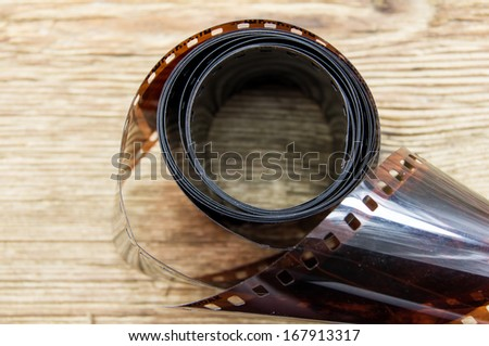 35mm negative films on wooden background - stock photo