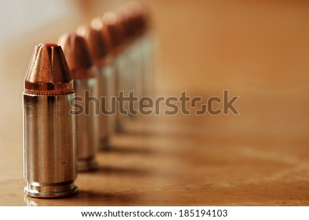 9mm polymer tipped bullets (used for concealed carry guns) on wood background.  Macro with shallow dof and copy space.  Selective focus limited to first bullet.  - stock photo