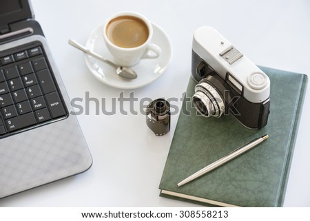 35mm vintage photocamera on diary with film, cup of coffee pen and notebook - stock photo