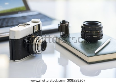 35mm vintage photocamera on table near lens, film and notebook - stock photo