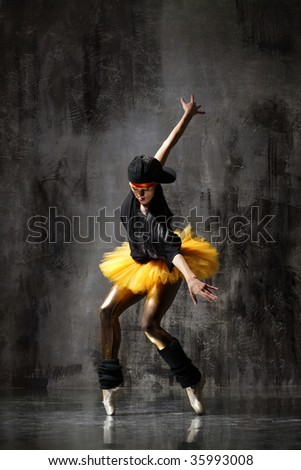 modern dancer poses in front of the old dirty wall - stock photo