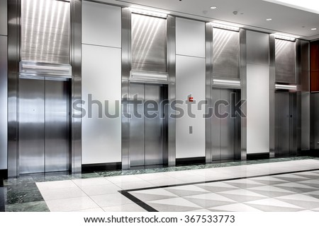 modern steel elevator cabins in a business lobby - stock photo
