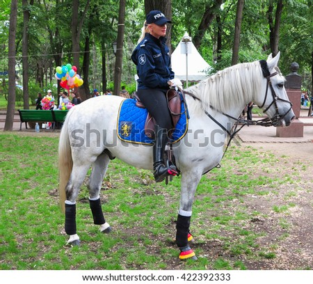 14.05.2016, Moldova, Lady policeman officer on a white horse in a park - stock photo