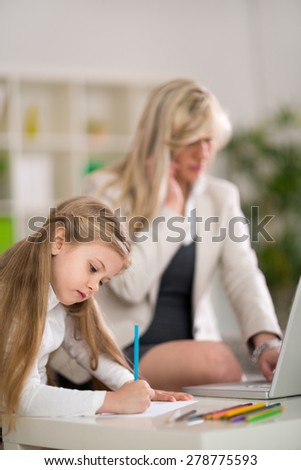 Mom and businesswoman working with laptop computer at home while her little daughter playing  - stock photo
