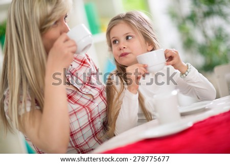 Mom and little daughter drinking tea together  - stock photo