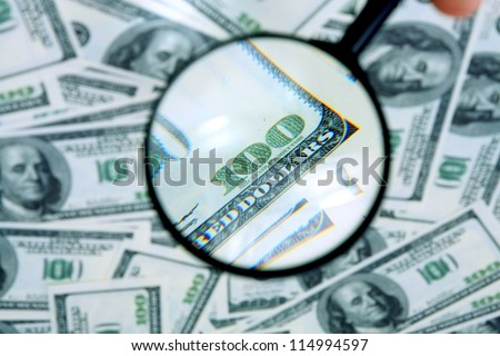 Money and magnifying glass - stock photo