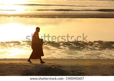 monk walking on the beach,Hua Hin Thailand - stock photo