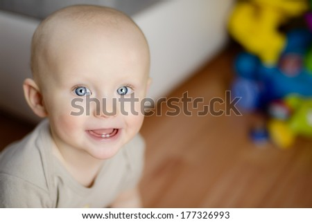 6 month baby showing his first two teeth laughing while having fun at home - stock photo