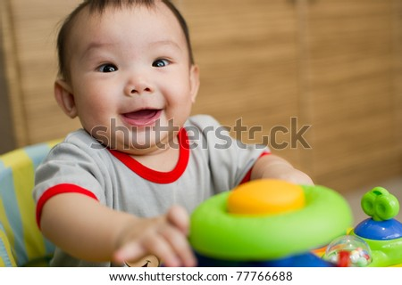 6 month old Asian baby girl smiling excitedly while sitting in a walker - stock photo