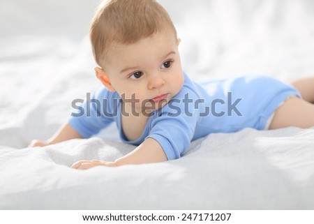 8-month-old baby boy laying on bed - stock photo