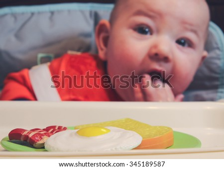 6 month old baby boy sitting in his high chair with a plate of pretend breakfast. Focus on breakfast plate. - stock photo
