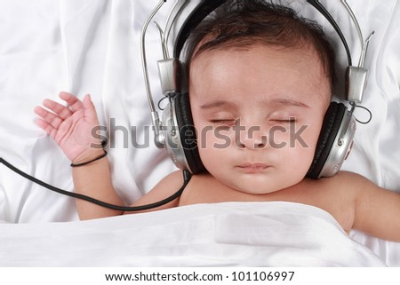 2 Month old baby listening to music with headphones - stock photo