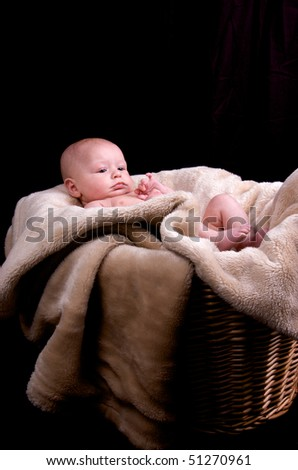 3 month old baby lying in a laundry basket with a blanket - stock photo