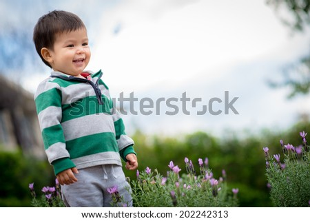 18 month old mixed race Asian boy plays happily outdoors in his suburban garden - stock photo