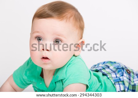 8 month year old baby lays on his stomach looking to the left surprised expression. dressed in a cute green polo shirt and blue plaid shorts. - stock photo