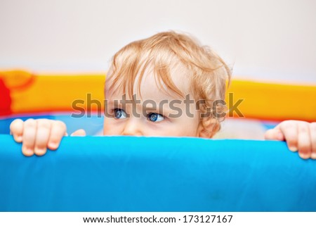 11 months Baby boy reaching out of his bed holding the edge with hands.  - stock photo