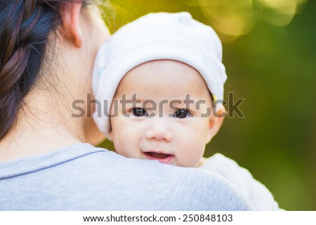 3 months baby feeling happy and smiles with her mother in the garden - stock photo