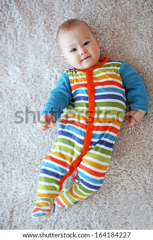 6 months baby lying down on a soft cozy carpet and looking at camera - stock photo