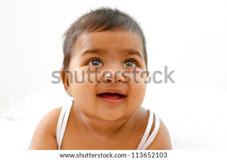 6 months old Indian baby girl having thought, looking up - stock photo