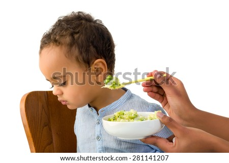 18 months old toddler refusing to eat his vegetables - stock photo