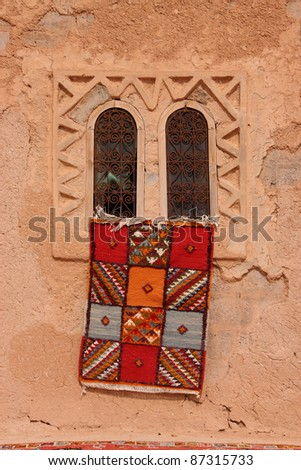 Morocco Essaouira  typical colorful Moroccan Berber carpet hanging from a beautiful window in an adobe wall - stock photo