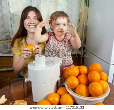 mother and daughter making fresh orange juice in home kitchen - stock photo