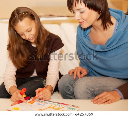 Mother and her daughter drawing together. - stock photo