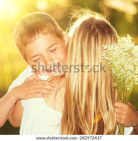 Mother and her little son with bouquet of flowers outdoors, Happy family mom and kid kissing and hugging. Mother's day gift.  - stock photo